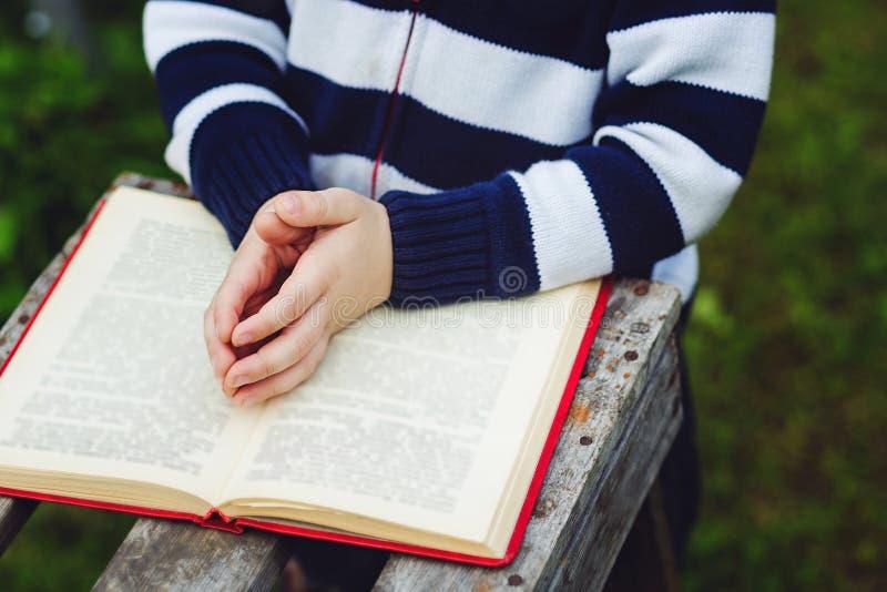 Le mani del bambino sopra sono piegate nella preghiera su una bibbia santa Concetto per fotografia stock libera da diritti