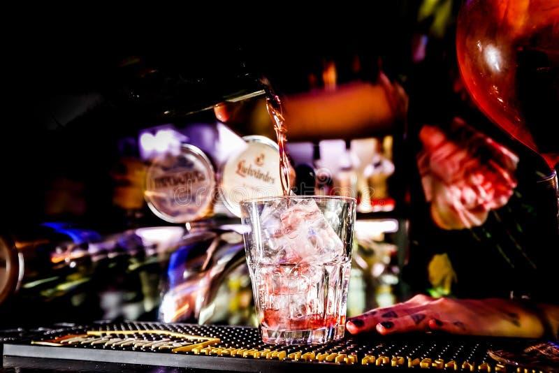 Le mani del barista che spruzzano l'alcool nel vetro di cocktail riempito di ghiaccio fotografia stock