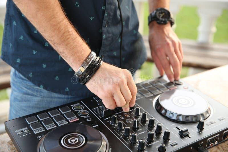 Le mani del DJ professionale sul regolatore mescolano la musica fotografia stock libera da diritti