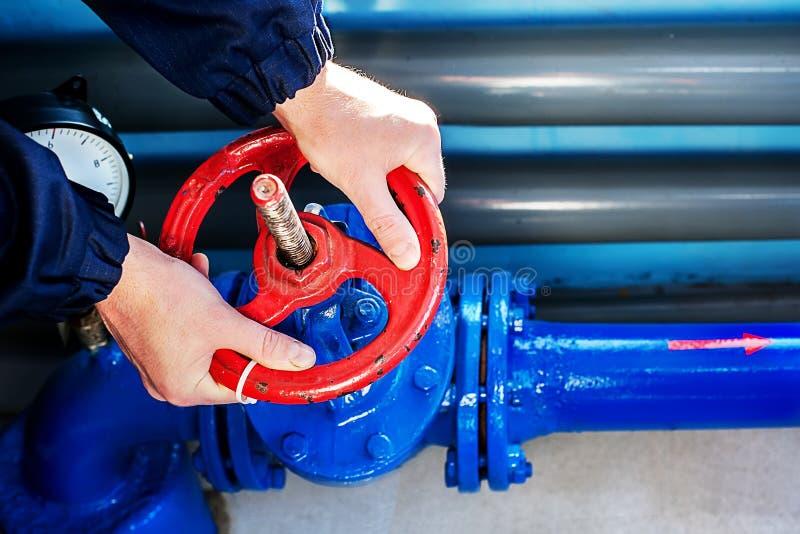Le mani del lavoratore Unscrew girano la valvola rossa per assicurare l'approvvigionamento di gas Primo piano di vista superiore fotografia stock libera da diritti