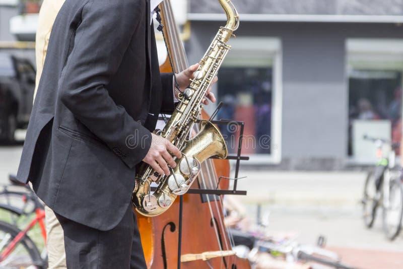 Le mani del musicista della via che giocano sassofono e contrabbasso in un ambiente urbano fotografia stock