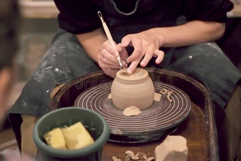 Le mani del padrone che lavora con l'argilla su un tornio da vasaio, primo piano immagini stock