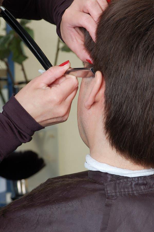 Le mani del parrucchiere radono un tempiale fotografia stock
