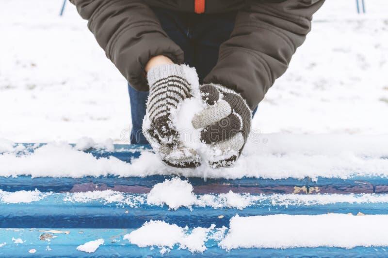 Le mani del ragazzo che indossano i guanti, guanti scolpisce le palle di neve, le attività all'aperto dell'inverno, concetto di s fotografia stock libera da diritti