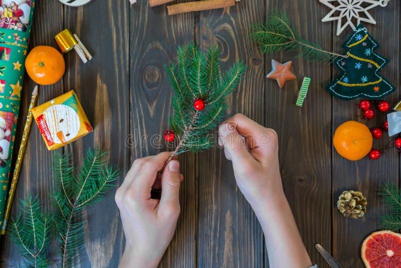 Le mani del ragazzo hanno tagliato il nastro rosso sui precedenti di legno decorazione della corona del nuovo anno immagine stock