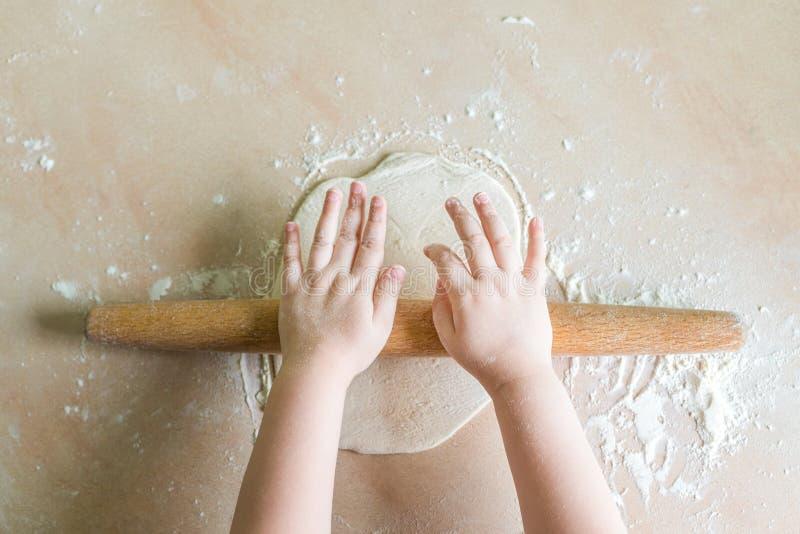 Le mani del ` s dei bambini hanno rotolato la pasta immagini stock