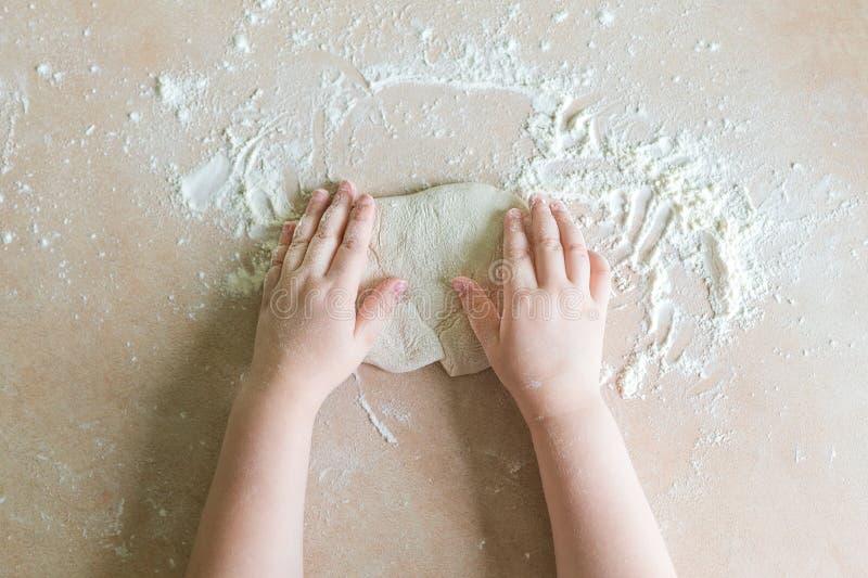 Le mani del ` s dei bambini producono la pasta fotografia stock libera da diritti