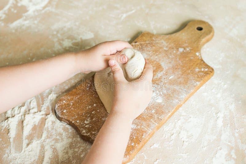 Le mani del ` s dei bambini producono la pasta fotografia stock