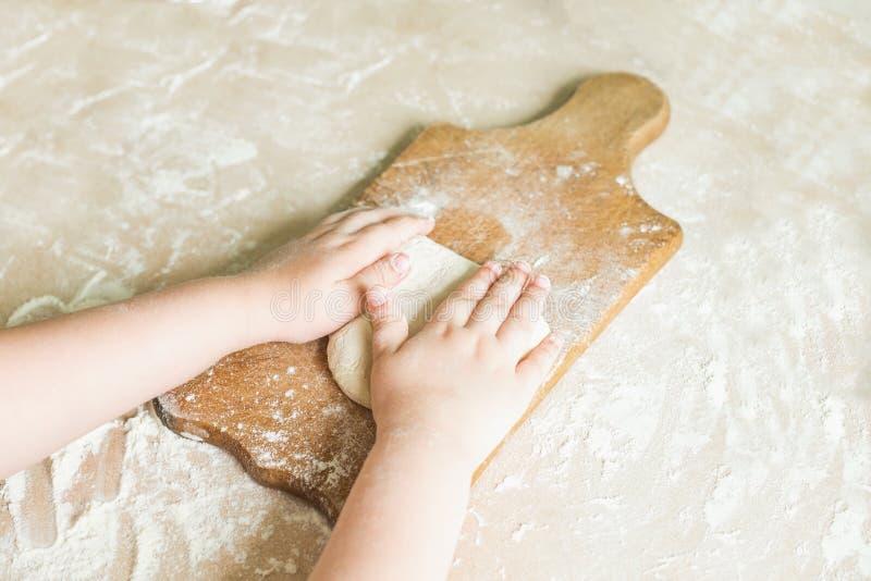 Le mani del ` s dei bambini producono la pasta fotografie stock