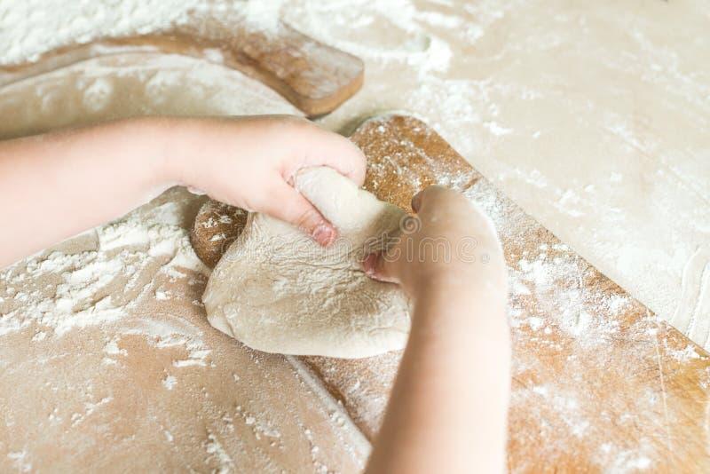 Le mani del ` s dei bambini producono la pasta immagini stock libere da diritti