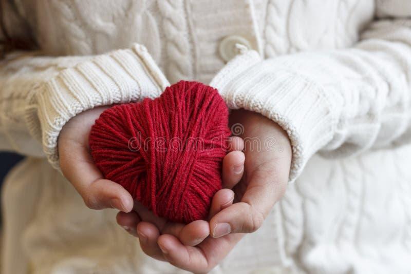 Le mani del ` s dei bambini tengono un cuore del filo rosso per tricottare fotografia stock libera da diritti