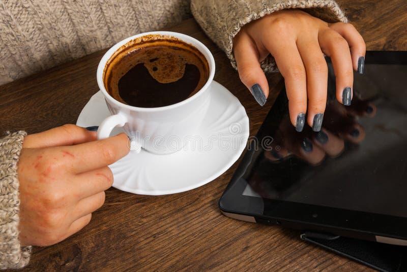 Le mani del ` s della donna in maglione che tiene la tazza di caffè e gli usi soppressione il dispositivo della compressa fotografia stock