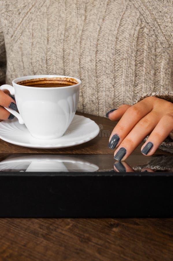 Le mani del ` s della donna in maglione che tiene la tazza di caffè e gli usi soppressione il dispositivo della compressa immagine stock libera da diritti