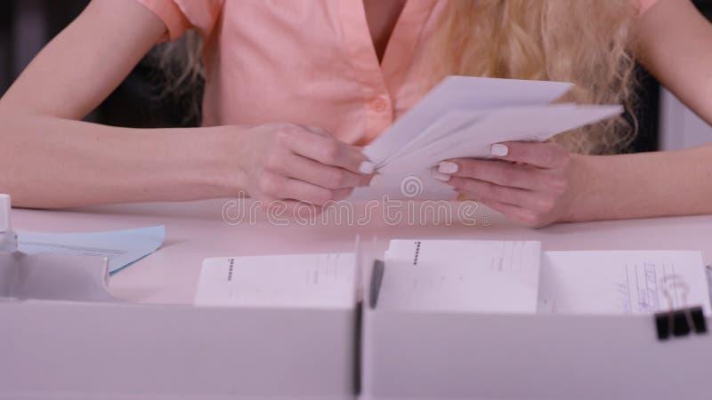 Le mani del ` s della donna ripetono sopra le lettere in buste Chiuda su delle buste che sono in mani di una donna invecchiata se immagine stock