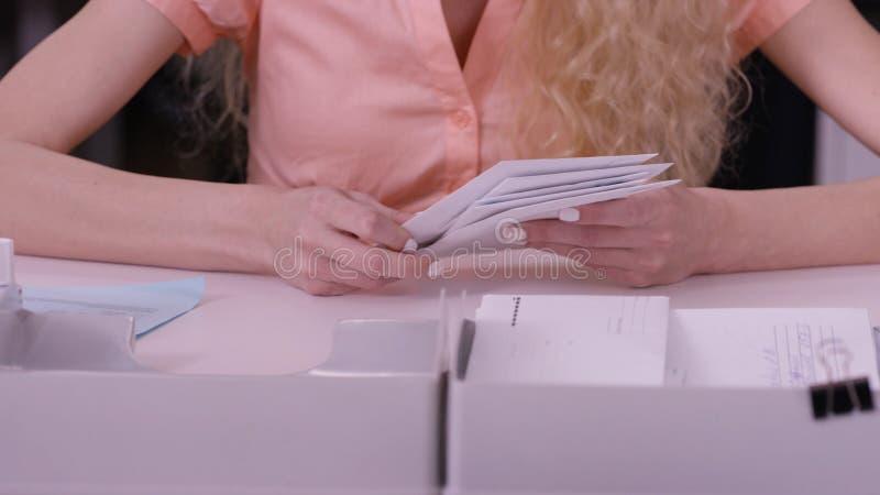Le mani del ` s della donna ripetono sopra le lettere in buste Chiuda su delle buste che sono in mani di una donna invecchiata se immagini stock