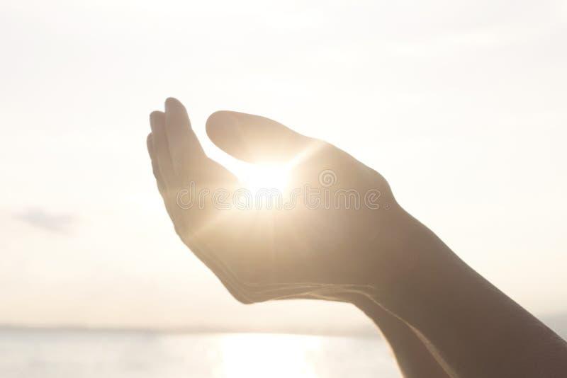 Le mani del ` s della donna tengono il sole e la sua energia fotografie stock libere da diritti