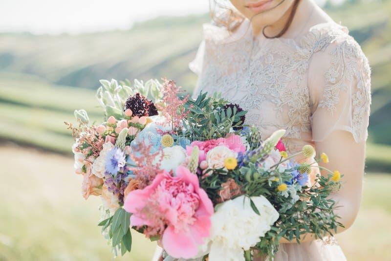 Le mani del ` s della sposa tengono il bello mazzo nuziale della peonia Fotografia di arte fotografie stock libere da diritti