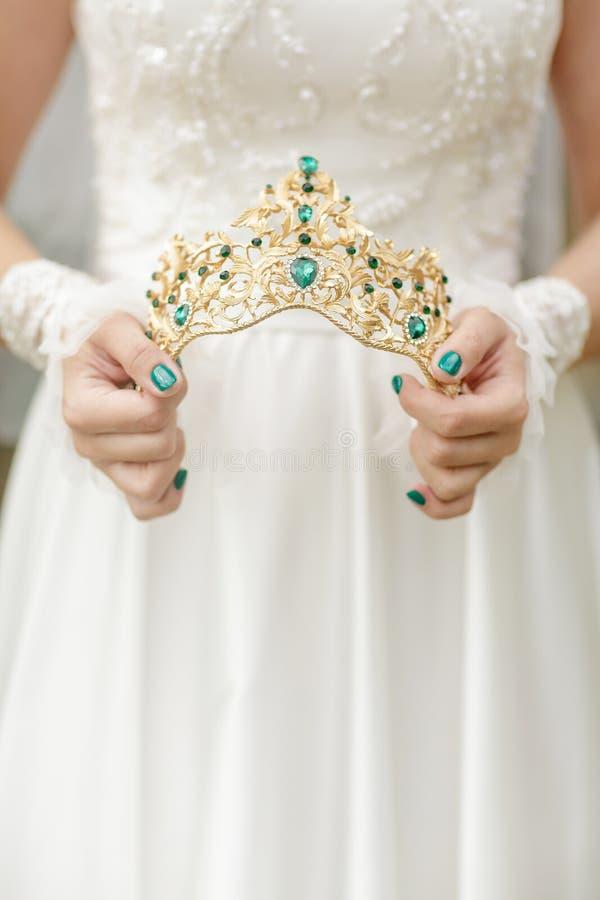 Le mani del ` s della sposa tengono la bella corona con le gemme verdi immagine stock