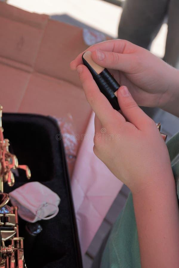 Le mani del ` s del giovane tengono la singola canna per il boccaglio del sassofono immagine stock