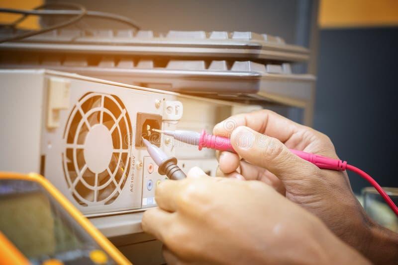 Le mani del tecnico di elettronica usano il controllo della penna del multimetro digitale fotografia stock libera da diritti