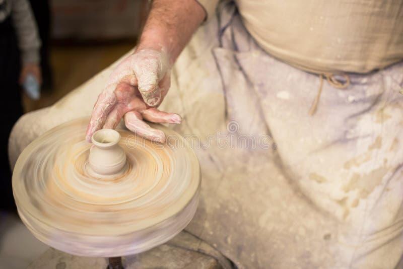 Le mani del vasaio al primo piano del lavoro Lavoricchii l'argilla di lavoro sulla ruota del ` s del vasaio fotografia stock libera da diritti