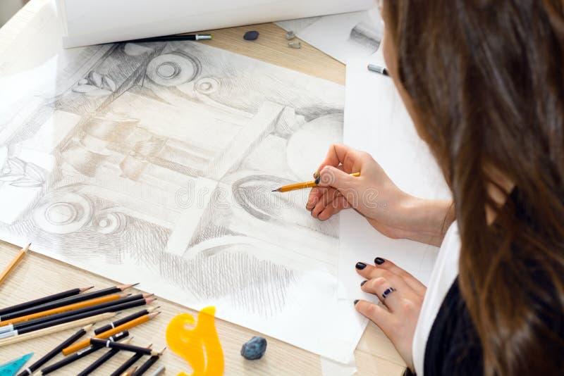 Le mani dell'architetto dello studente con una matita che prepara un modello di luce e di ombra, primo piano di asta della ringhi fotografie stock