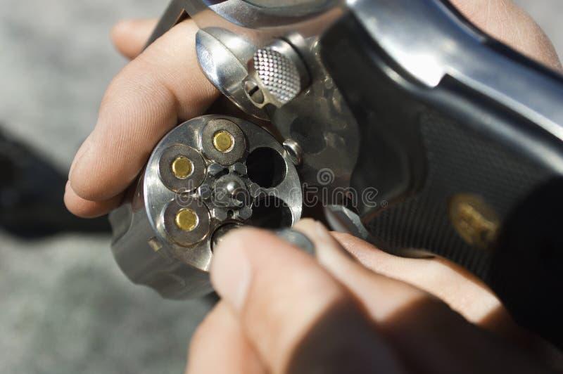 Le mani dell'uomo che caricano le pallottole nella pistola fotografia stock