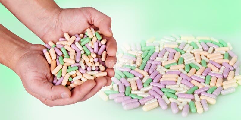 Le mani dell'uomo che giudicano le pillole variopinte isolate su fondo bianco fotografie stock