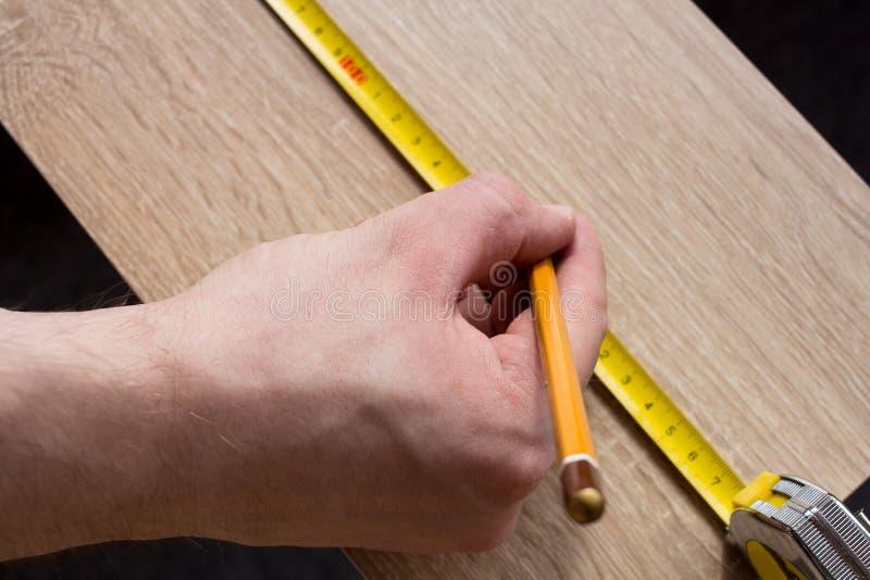 Le mani dell'uomo che misurano plancia di legno con una linea del nastro fotografia stock