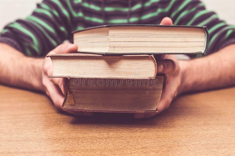 Le mani dell'uomo che tengono alcuni vecchi libri fotografia stock