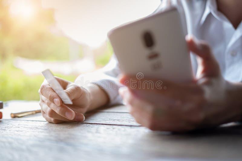 Le mani dell'uomo che tengono una carta di credito e che per mezzo dello Smart Phone per l'acquisto online, pagamento online fotografie stock
