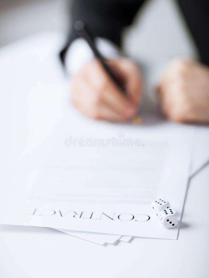 Le mani dell'uomo con il gioco taglia il contratto a cubetti di firma fotografia stock