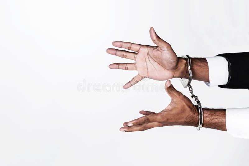Le mani dell'uomo d'affari hanno impastoiato con le manette isolate su bianco con fotografia stock libera da diritti