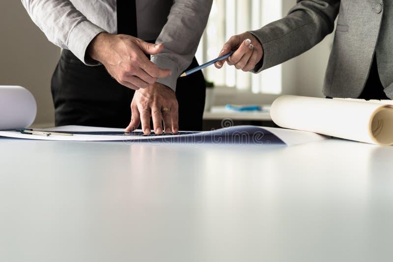 Le mani dell'uomo d'affari offrono la matita all'architetto che lavora ai piani fotografie stock