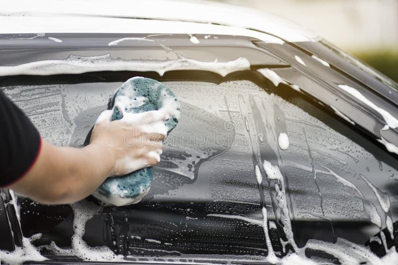 Le mani dell'uomo tengono con l'automobile blu di lavaggio della spugna fotografia stock