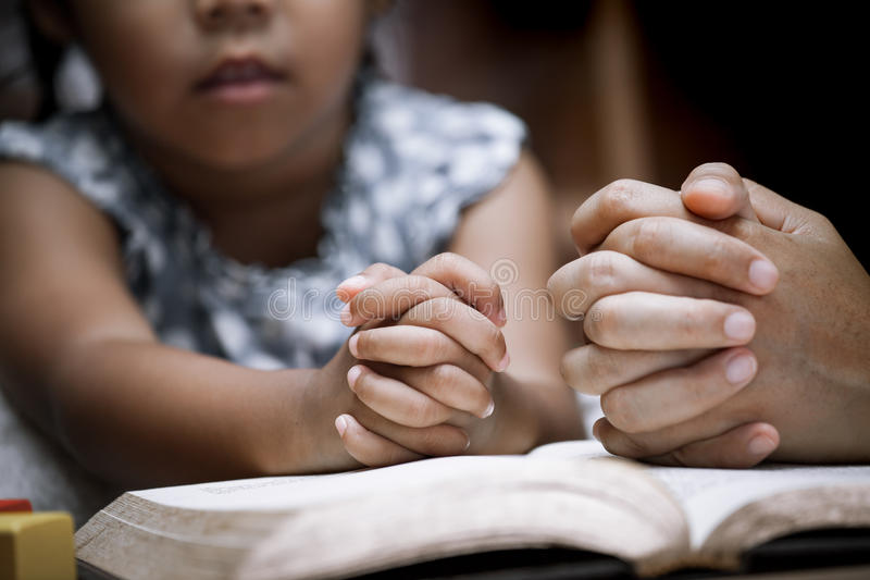 Le mani della bambina e della madre hanno piegato nella preghiera su una bibbia santa fotografia stock libera da diritti