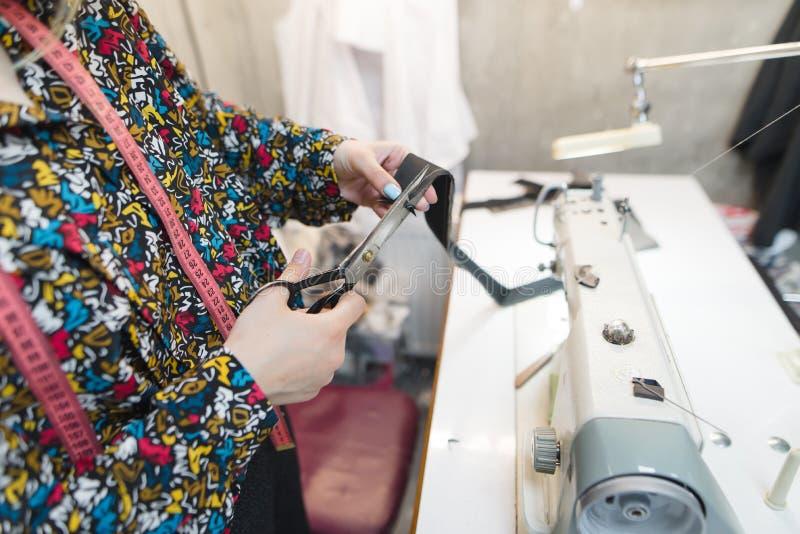 Le mani della cucitrice hanno tagliato il tessuto con le forbici sui precedenti della macchina per cucire e del posto di lavoro immagine stock