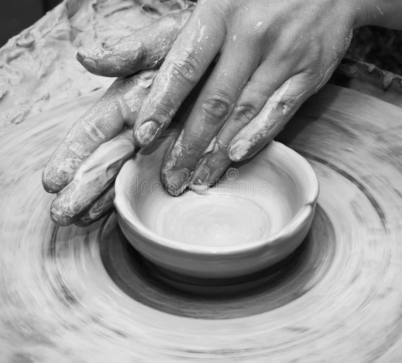 Le mani della donna in argilla al processo di fabbricazione dell'argilla lanciano sul wh delle terraglie immagine stock
