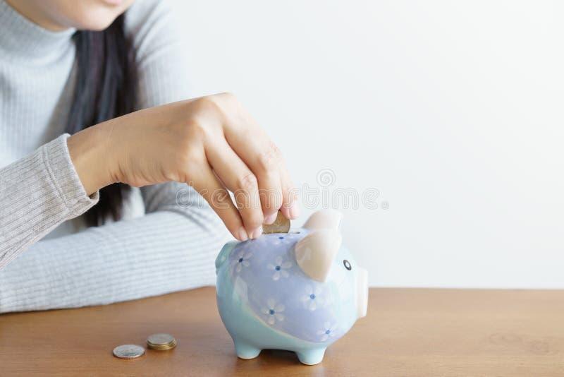 Le mani della donna che mettono il porcellino delle monete risparmiano i soldi per l'investimento Concetto dei soldi di risparmio fotografie stock libere da diritti