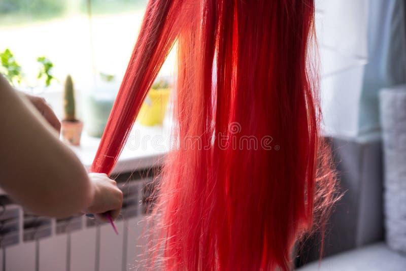 Le mani della donna che pettinano delicato capelli rossi, parrucca sudicia sul supporto fotografia stock