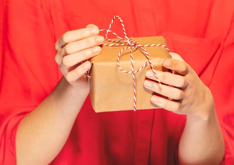 Le mani della donna che sciolgono l'arco del pizzo sul regalo di Natale fotografia stock