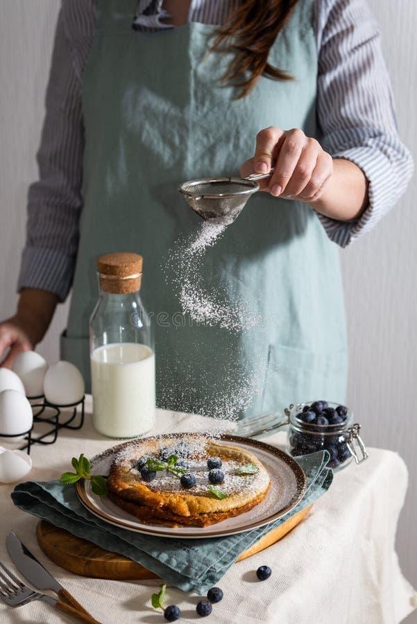 Le mani della donna che spruzzano zucchero in polvere su un pancake olandese casalingo del bambino con i mirtilli, la menta e lo  fotografia stock libera da diritti