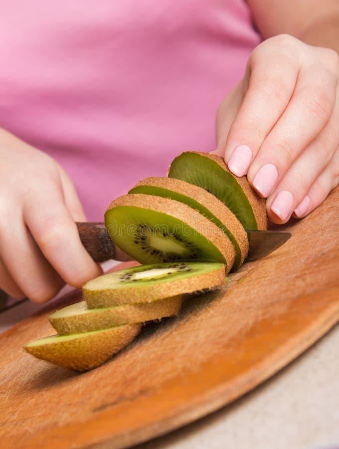 Le mani della donna che tagliano kiwi fresco immagine stock