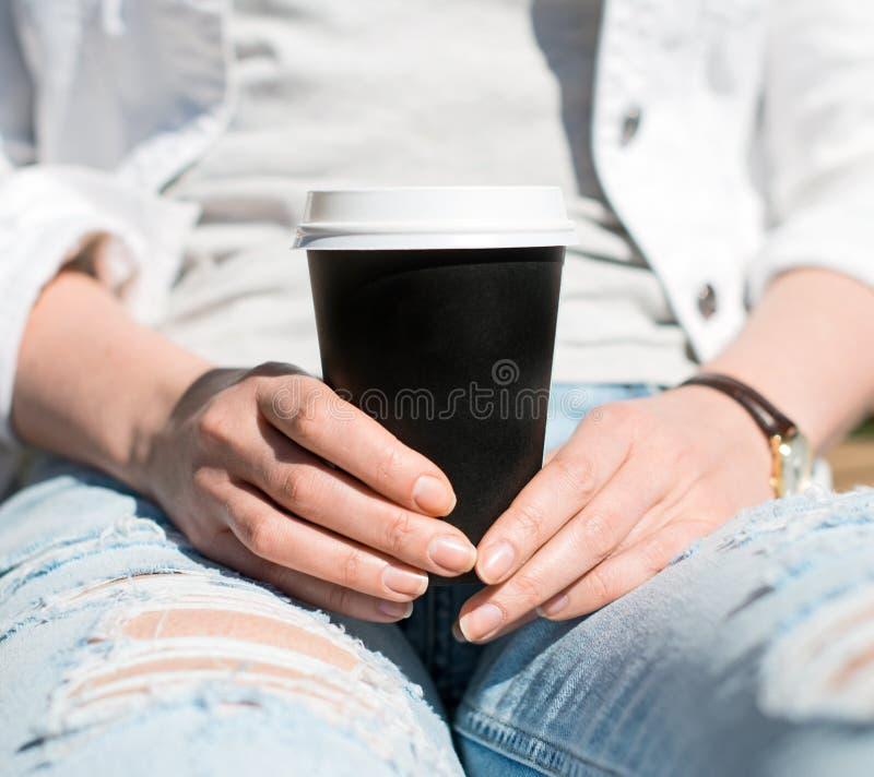Le mani della donna che tengono caffè fotografia stock libera da diritti