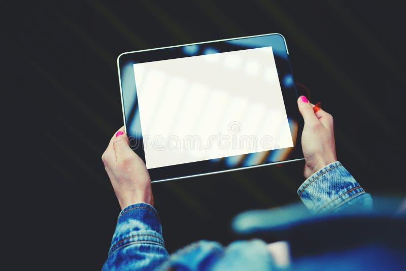 Le mani della donna che tengono compressa digitale con il For Your Information o il contenuto in bianco dello schermo dello spazi immagine stock