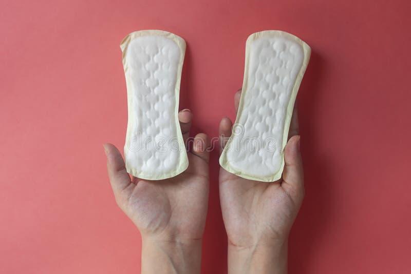 Le mani della donna che tengono due cuscinetti femminili di igiene Mani dei cuscinetti mestruali della tenuta femminile o dei tov immagine stock libera da diritti