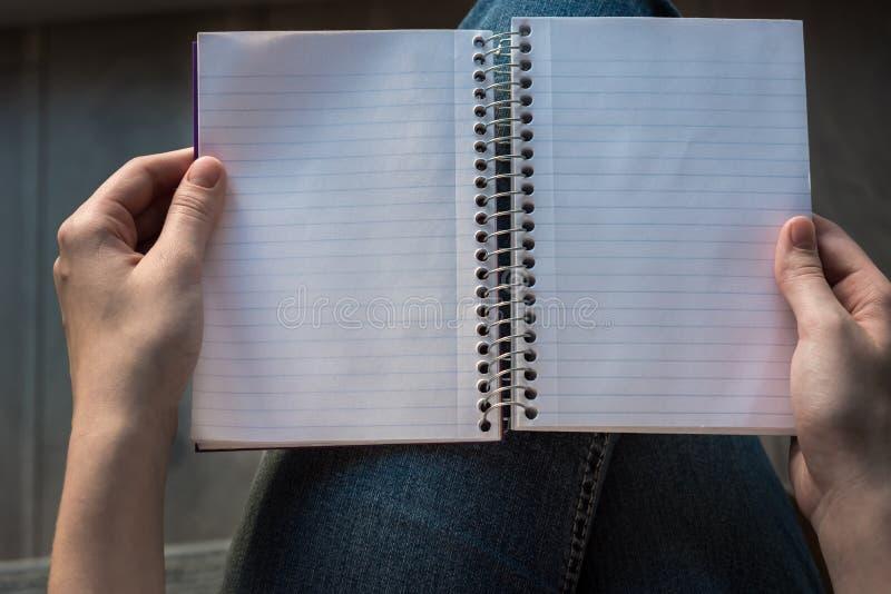 Le mani della donna che tengono taccuino allineato aperto con le pagine allineate sul rivestimento fotografia stock