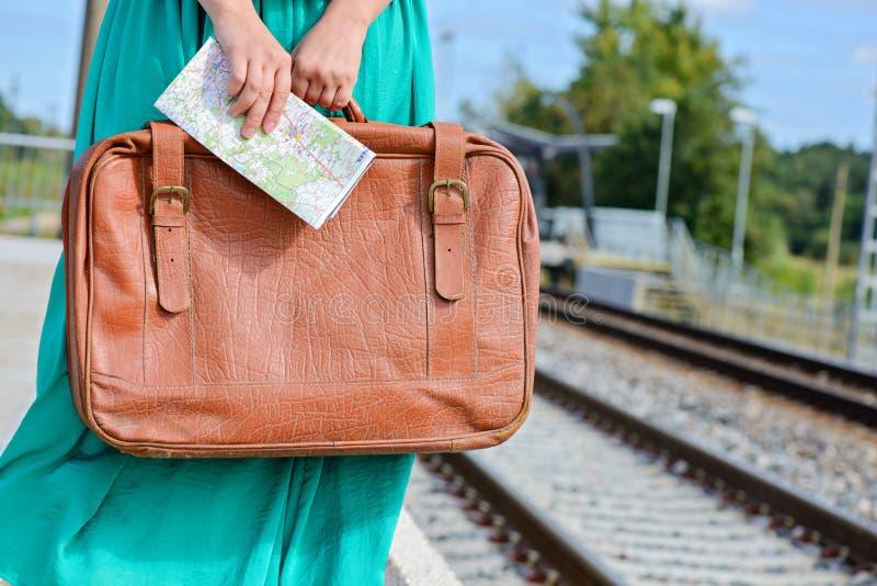 Le mani della donna che tengono una mappa e una valigia alla stazione fotografia stock libera da diritti
