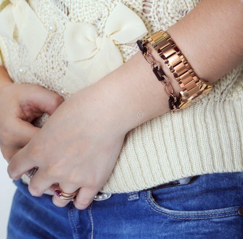 Le mani della donna con gli anelli dorati, il braccialetto e un orologio dorato fotografie stock