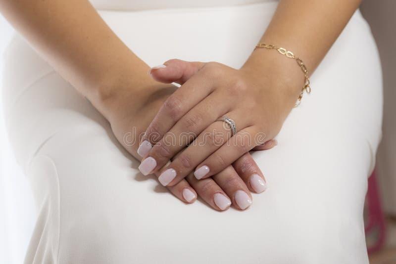 Le mani della donna con l'anello di fidanzamento per la celebrazione di nozze immagini stock libere da diritti